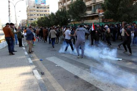 Protesters run from tear gas fired by security forces after supporters of Iraqi Shi'ite cleric Moqtada al-Sadr tried to approach the heavily fortified Green Zone during a protest at Tahrir Square in Baghdad, Iraq.